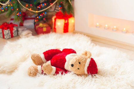 sorrowfully: Forgotten gift. Santa teddy bear toy lie on sheepskin rug near illuminated christmas tree. Vibrant multicolored indoors horizontal image.
