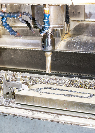 mounting holes: Industrial metal moldblank speed drilling. Metalworking, mechanical engineering, lathe and milling technology. Indoors vertical image.