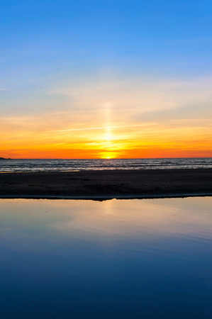 water's edge: Multicolored summertime sunset on Baltic sea beach. Blue sky background. Vertical outdoors image
