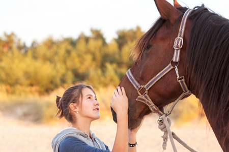 domestic animals: Young cheerful teenage girl stroking her big lovely horses nose. Vibrant multicolored summertime outdoors horizontal image.