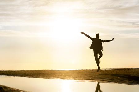 persone che ballano: Silhouette giovane ragazza che balla in raggio di sole al tramonto sulla spiaggia. all'aperto vibrante immagine orizzontale. costa del Mar Baltico. Archivio Fotografico
