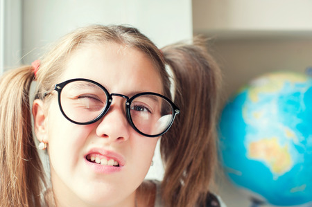 slovenly: Neglecting the school. Nerdy funny girl with ponytails in eyeglasses. Indoors vibrant closeup horizontal image.