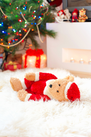 sorrowfully: Forgotten gift. Santa teddy bear toy lie on sheepskin rug near illuminated christmas tree. Multicolored indoors vertical image.