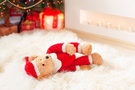 sorrowfully: Forgotten gift. Santa teddy bear toy lie on sheepskin rug near illuminated christmas tree. Multicolored indoors horizontal image. Stock Photo