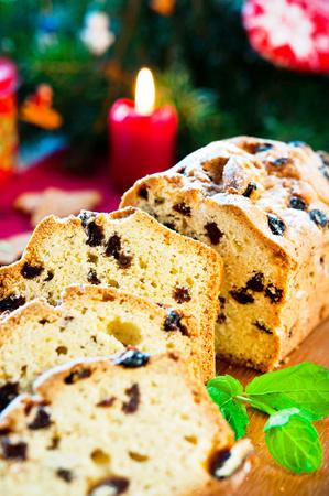 fruitcake: Festive sliced christmas fruitcake with raisins and mint leaf on christmas background. Indoors multicolored vertical close-up image. Stock Photo