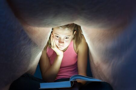 Young teenage girl hiding under blanket and enrapt reading interesting book at nighttime. Key light coming from book. Indoors horizontal image. Stock Photo