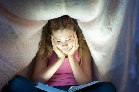 obscurity: Young cheerful teenage girl hiding under blanket and enrapt reading interesting book at nighttime. Key light coming from book. Indoors horizontal image. Stock Photo
