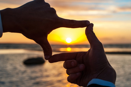 Composition finger frame- mans hands capture the sunset. Multicolored horizontal outdoors image. Stock Photo