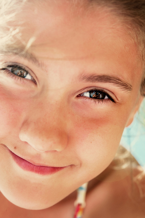 beautiful sunshine: Low angle view of beautiful  smiling playful girl closeup portrait. Vibrant summertime vertical image.