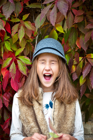 Portrait of funny yawning girl. Autumn decorative grape background. Multicolored vertical outdoors image. Stock Photo