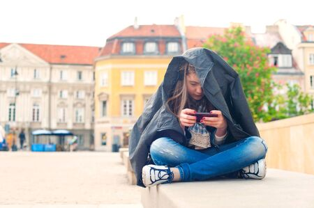 Teenage problems. Young girl addicted to social media technologies. Multicolored summertime outdoors horizontal image. Archivio Fotografico