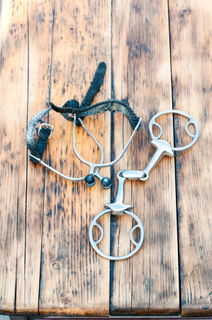 spurs: Steel horse snaffle-bit and spurs, on wooden background. Outdoors vertical close-up image. Stock Photo