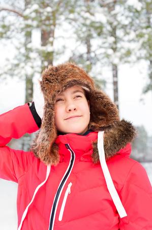 ni�as sonriendo: adolescente alegre en la orejera caliente que se divierten en el bosque de invierno. Multicolores aire libre vibrantes imagen vertical.