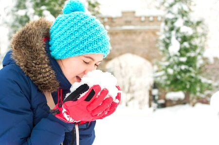 heap of snow: Young cheerful teenage girl holding heap of soft snow in her arms. Bright outdoors horizontal image.