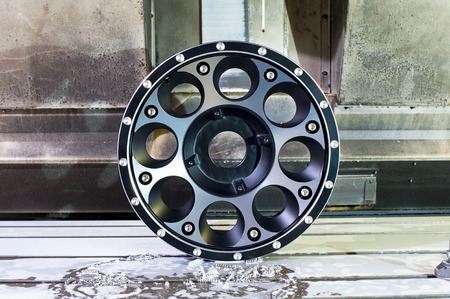 chrome base: Round car alloy black new rim die mounting in milling and lathe cnc machine. Front view of working process. Mechanical engineering and metalworking industry. Horizontal indoors image. Stock Photo