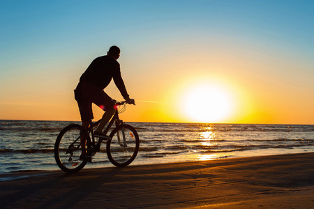 people in action: Young man cyclist silhouette on blue sky and sunset background on the beach. Summertime multicolored outdoors horizontal image with filter. Stock Photo