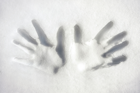 empty handed: Both handspalms print on white snow surface. Outdoors closeup horizontal image