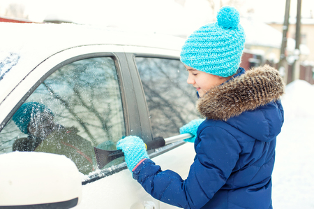 scraping: Young teenage girl scraping ice on car window from winter snow in january. Bright outdoors horizontal image Stock Photo