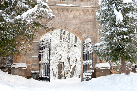 sigulda: Antique stone gates  covered with snow in Sigulda, Latvia. Bright outdoors horizontal image.