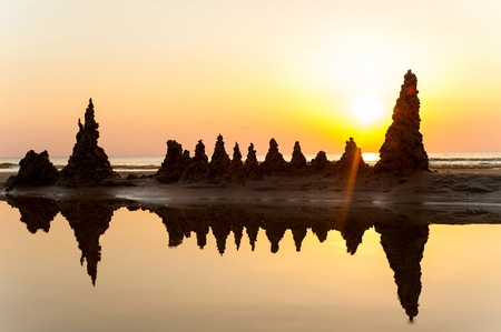 Beach with sandcastles on spectacular Baltic sea sunset background in Latvia. Multicolored summertime outdoors horizontal image. Copy space.