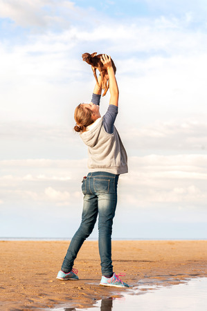 Young cheerful teenage girl holding high up her lovely little Toy-terrier dog. Vibrant summertime outdoors vertical image. Stock Photo