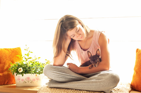 toyterrier: Good morning! Young girl in pyjamas holding her lovely Toy-terrier dog in rays of sunlight. Multicolored vibrant horizontal indoors image with filter.
