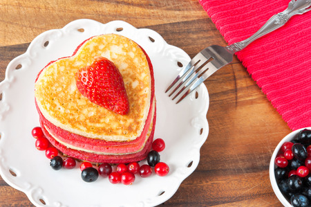 Festive dish-Valentines day homemade colored heart shaped pancakes with berries. Vibrant indoors horizontal closeup image. Stock Photo