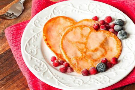 Homemade pink colored Heart shaped pancakes with cranberries on white  porcelain plate. Celebration festive dessert. Multicolored indoors closeup horizontal image