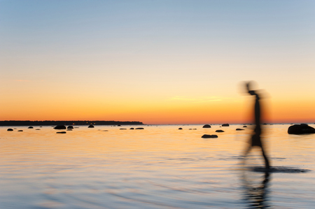 Man defocused silhouette walking in sea water at multicolored sunset background. Long exposure. Outdoors vibrant horizontal image.