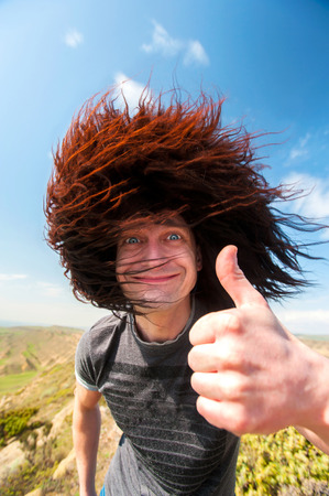Welcome to Caucasus! Portrait of smiling funny man in black sheep-hat showing thumb up-ok sign in mountains. Colorful vibrant outdoors vertical image.