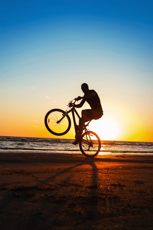 Young man cyclist silhouette on blue sky and sunset background on the beach. Summertime multicolored outdoors vertical image with vintage filter. Stock Photo