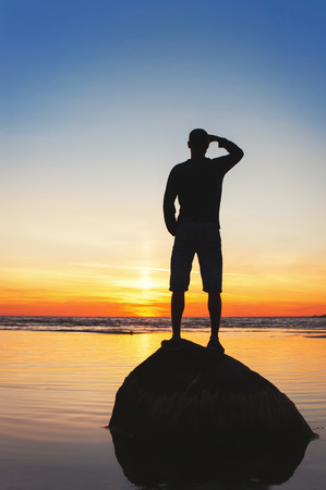 Young man silhouette standing on the rock at multi-colored sunset background. Summertime vibrant outdoors vertical image with filter. Copy space.