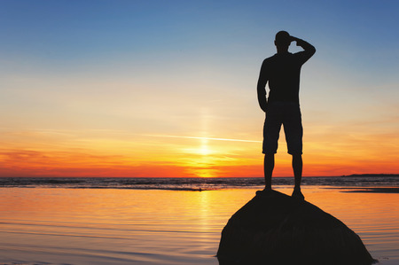Young man silhouette looking out on the rock at multi-colored sunset background. Summertime vibrant outdoors horizontal image. Vintage filter. Copy space. Standard-Bild