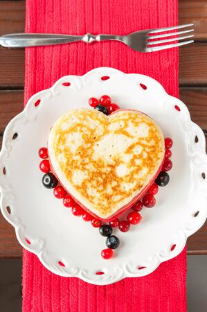Homemade colored heart shaped pancakes with berries on white  porcelain plate. Celebration festive dessert. Multicolored indoors closeup vertical image Stock Photo