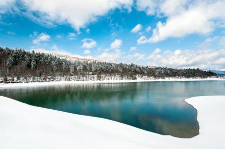 Frozen lake and snowy woodland in winter Georgia. Shaori lake, Racha. Caucasus. Colorful vibrant outdoors horizontal image.