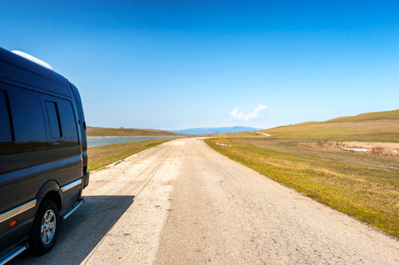 Road to the mountains. Black minibus standing in Georgian fields. Colorful summertime outdoors horizontal image with perspective.
