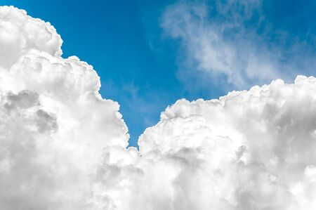 White fleecy cumulus congestus clouds on blue sky background. Vibrant multicolored outdoors horizontal image with copy space.