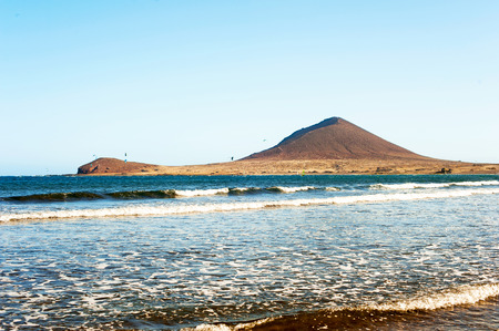 abilities: Atlantic ocean coast with Montana Roja on background. El Medano, Canary islands, Tenerife, Spain. Vibrant multicolored summertime horizontal outdoors image. Stock Photo
