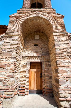 Antique historical wooden door in stone enter arcade in David Gareji monastery complex on Geargian-Azerbaijan border ridge. Colorful summertime vibrant outdoors vertical image on blue cloudy sky background. Stock Photo