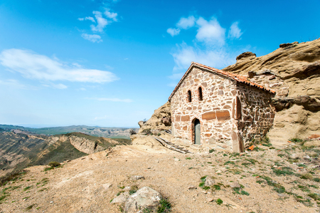 Antique historical church built in cliff in David Gareji monastery complex on Geargian-Azerbaijan border ridge. Colorful summertime vibrant outdoors horizontal image on blue cloudy sky background.