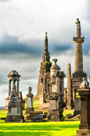 Glasgow Necropolis. Scottish ancient cemetery on blue dramatic cloudy sky background. Summertime outdoors. Stock Photo