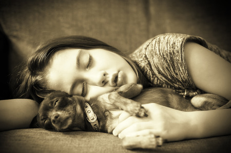 toyterrier: Sweet dreaming. Little girl sleeping with her small favorite toy-terrier dog together on a coach. Monochrome horizontal indoors image.