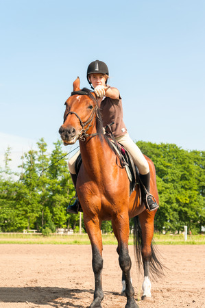 Young teenage girl equestrian riding horseback on chestnut horse. Multicolored outdoors vertical image. Stock Photo