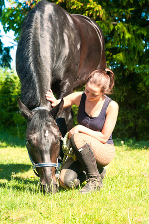 Young lady equestrian sitting and stoking her dark horse on green grass. Vibrant multicolored summertime outdoors vertical image.