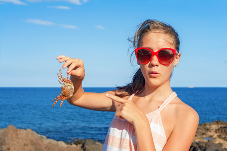 Funny wondering glad teenage girl in red sunglasses holding an atlantic crab on ocean coast. Blue sky background. Multicolored summertime outdoors image. Stock Photo