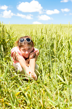 toyterrier: Young teenage girl sitting in wheat field holding her lovely little toy-terrier dog. Multicolored vibrant outdoors summertime vertical image with cloudy sky background.