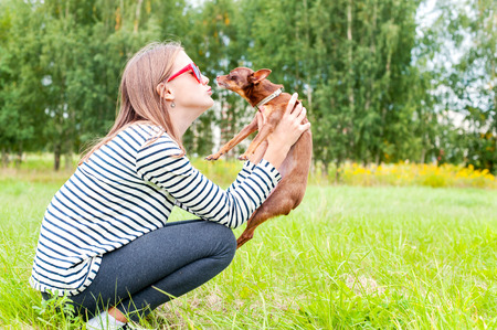 Unconditional love. Teenage girl sitting on grass in summer green park and  kissing her little brown toy-terrier dog. Multicolored outdoors horizontal image. Stock Photo