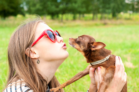 toyterrier: Unconditional love. Teenage girl kissing her little brown toy-terrier dog. Multicolored summertime outdoors horizontal image.