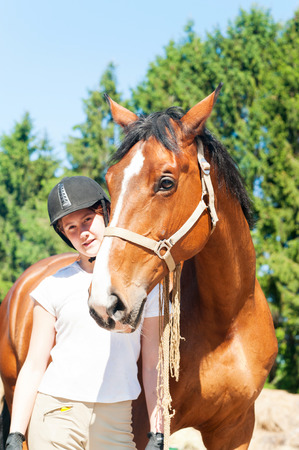 Young cheerful teenage girl equestrian standing with her brown horse. Multicolored vibrant outdoors vertical summertime image.