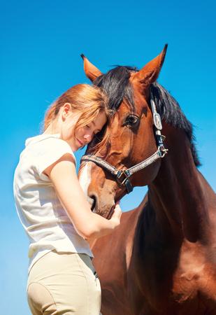 yegua: Chica joven pelirroja adolescente que abraza su caballo castaño favorita con amor. Vibrante imagen al aire libre color vertical con filtro. Foto de archivo